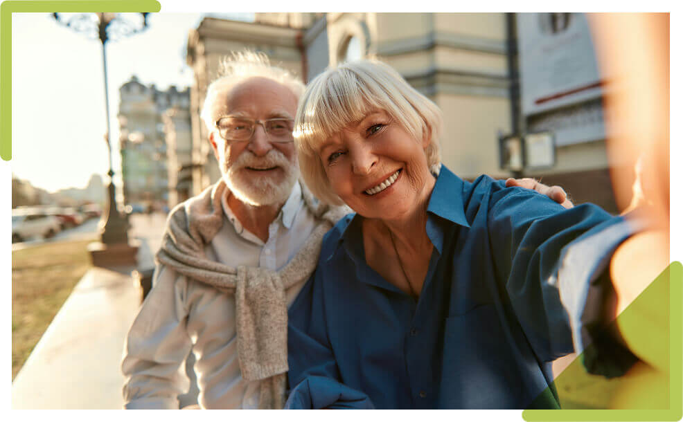 An elderly couple taking a selfie while outside walking.