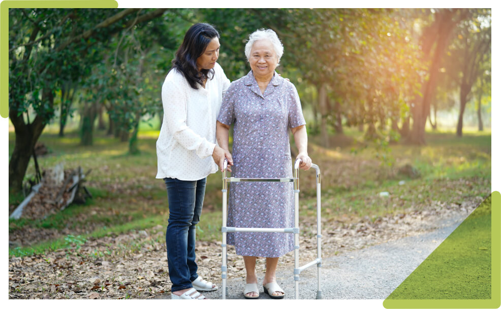 home support worker taking an elderly client for a walk.
